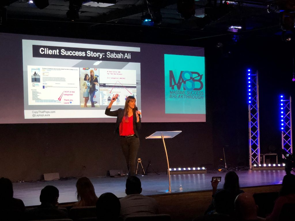 Laptop Laura Petersen speaking on stage about hitting best selling author